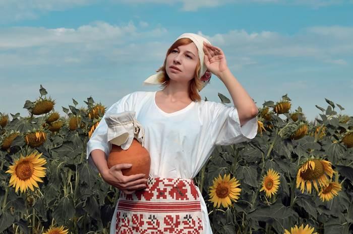 Девушка с крынкой в поле подсолнухов